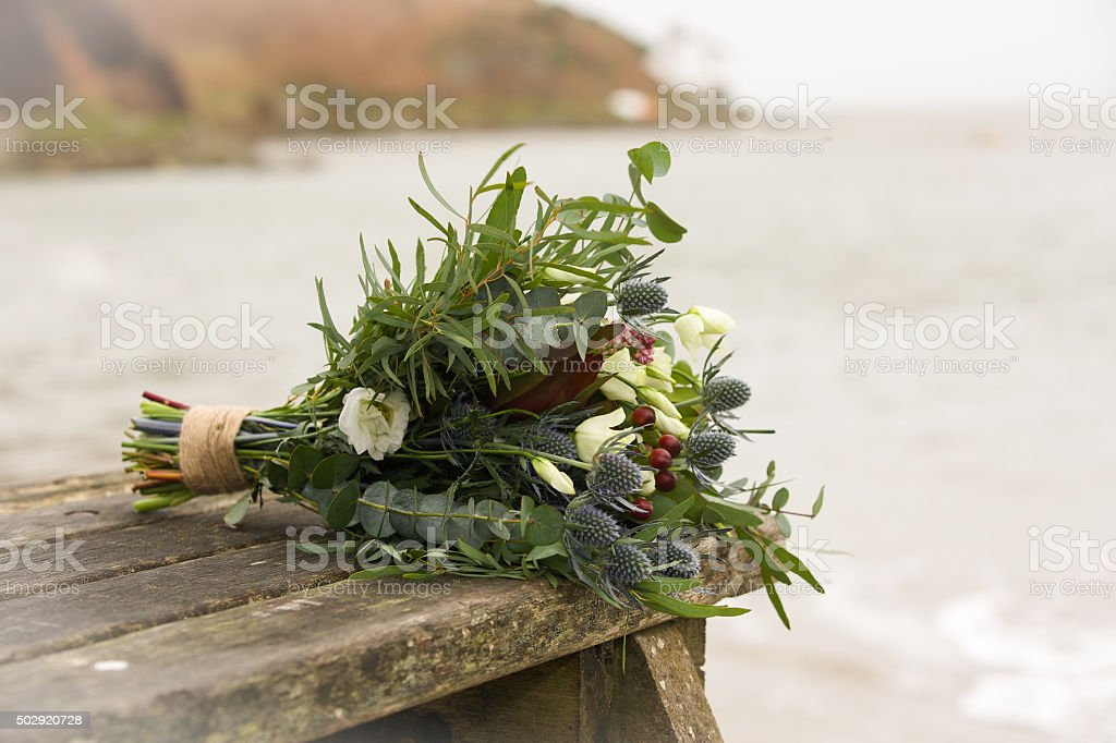 Wedding flower bouquet strung together on a wooden bench stock photo