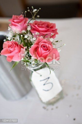 Pink roses in a glass jar used as a table decoration at a wedding