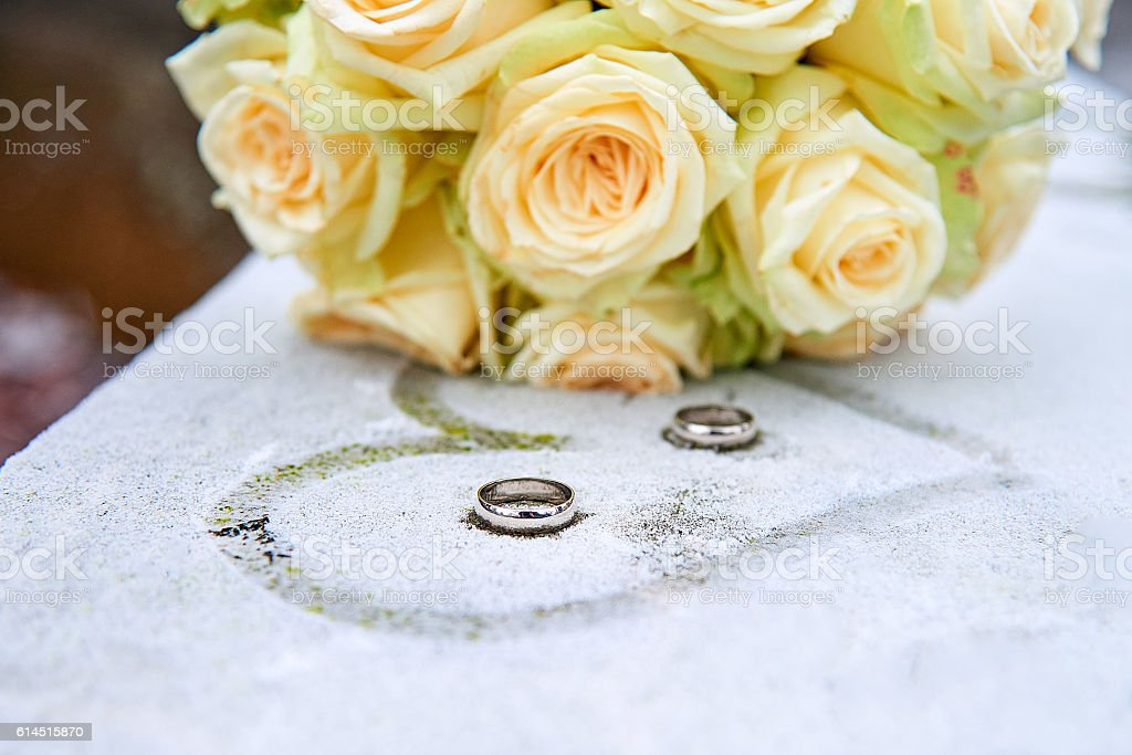 Wedding flowers and rings on frozen surface stock photo