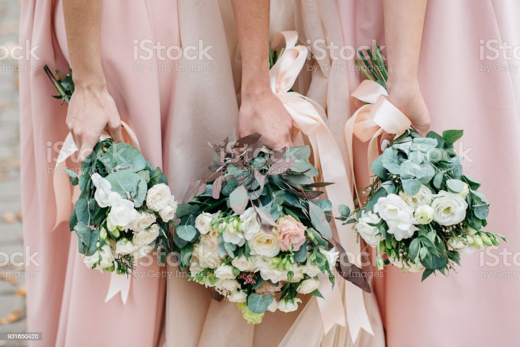 Wedding flowers in hand the bride and her bridesmaids. stock photo