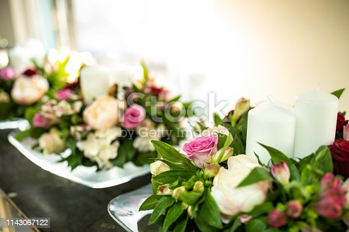 Beautiful wedding flower arrangement  with candles at florist workshop
