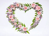 istock Wedding frame of flowers in heart-shaped: rose, lilac, rowan leaves on a white background. Floral pattern. Copy space for text 1156885493