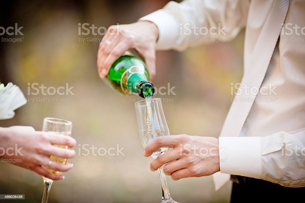 Wedding glasses of champagne in groom's hands stock photo