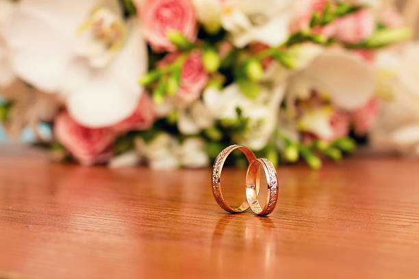 wedding gold rings and pink flowers stock photo