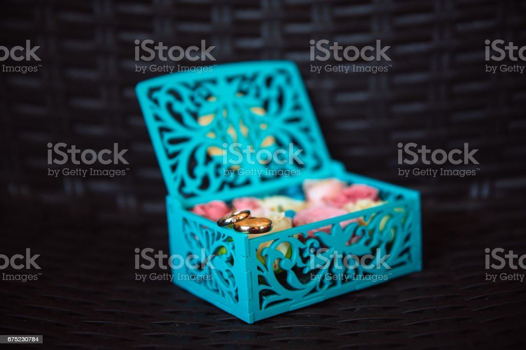 Wedding gold rings in a blue wooden box on the dark background. Concept of love royalty-free stock photo