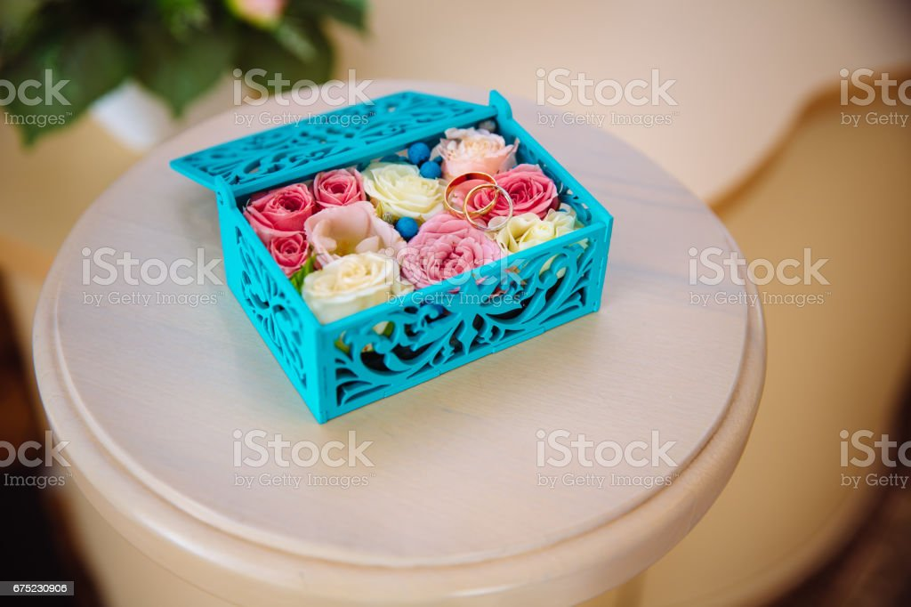 Wedding gold rings in a blue wooden box on the white table background. Concept of love royalty-free stock photo