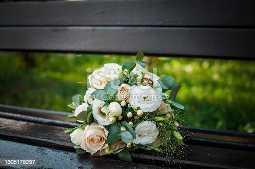 istock Wedding gold rings on a bouquet with white roses 1305175297