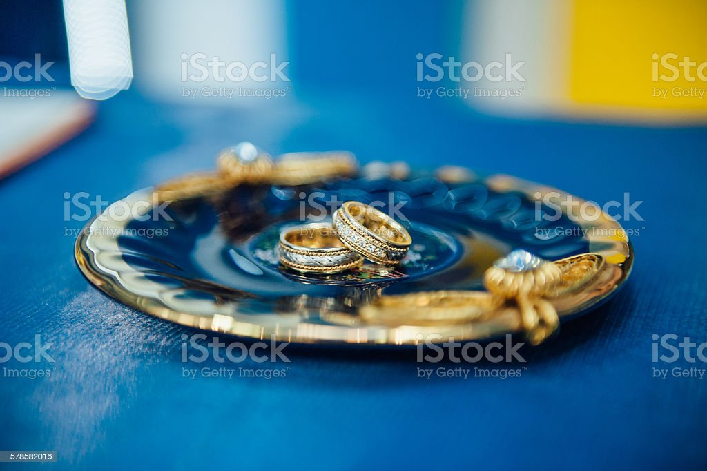 wedding gold rings on a silver plate stock photo