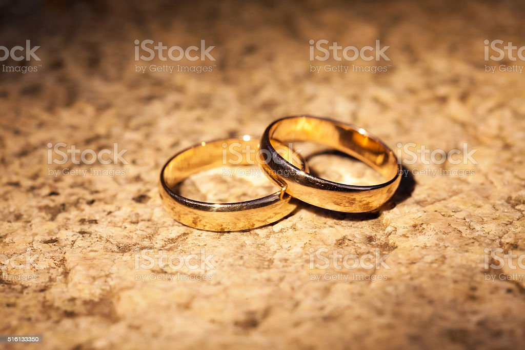 Wedding gold rings on the stone stock photo
