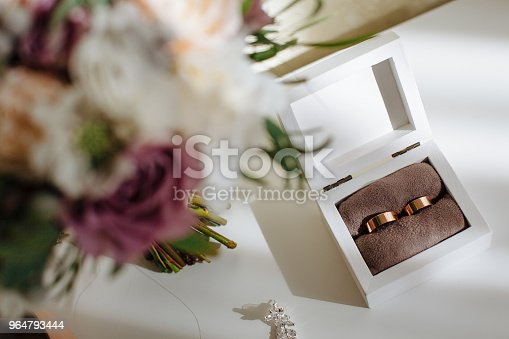 istock wedding golden wide rings in wooden box and bouquet with beautiful roses. Preparation. 964793444
