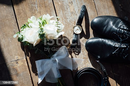625840656 istock photo Wedding groom accessories. Shoes, bouquet, belt and socks in a top view. 1084872580