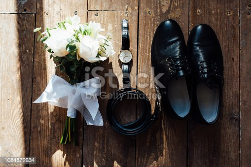 625840656 istock photo Wedding groom accessories. Shoes, bouquet, belt and socks in a top view. 1084872634
