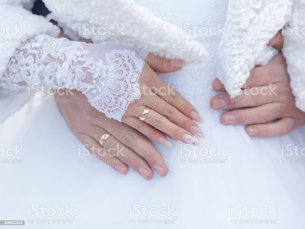 Wedding Hands With Wedding Rings On Fingers Against White Wedding