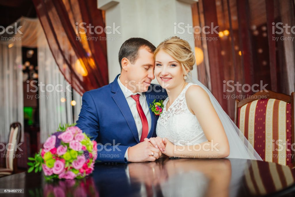 Wedding. Happy bride and elegant groom holding hands while sitting next to each other in luxury apatment. Wedding day. royalty-free stock photo