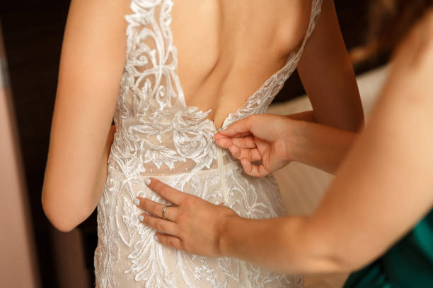 Wedding help. Bridesmaid dresses a wedding dress for the bride in the fitting room stock photo
