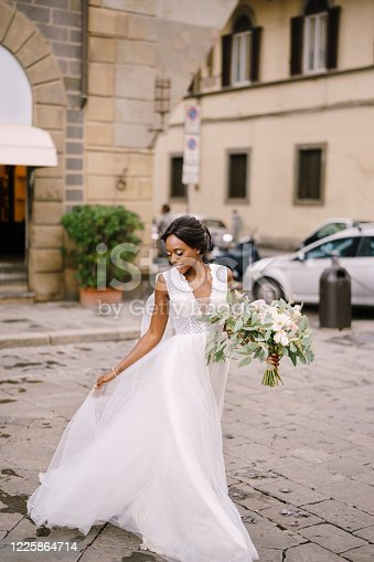African-American bride in a white dress with a long veil and bouquet in hand. Wedding in Florence, Italy.