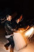 Wedding in the style of rock. Rocker or Biker wedding. Guys with stylish leather jackets. It's a rock'n'roll baby! Sweet couple are running with Bengal lights and fireworks in their hands.