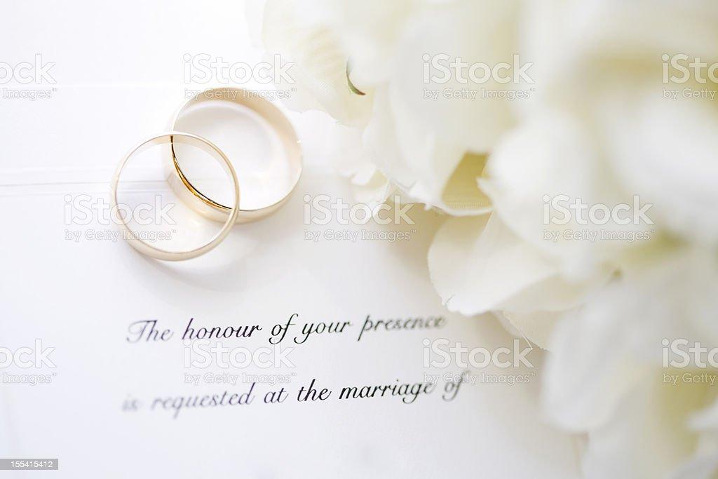 Wedding invitation and rings stock photo
