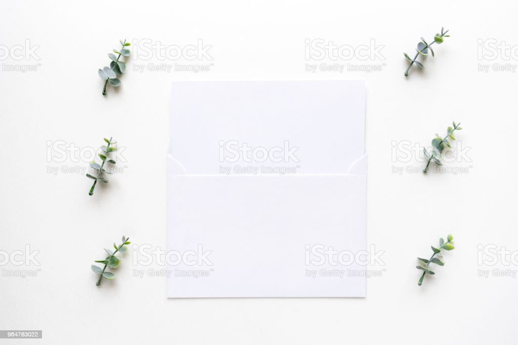 Wedding invitation card and oregano branches on white marble. Top view. royalty-free stock photo