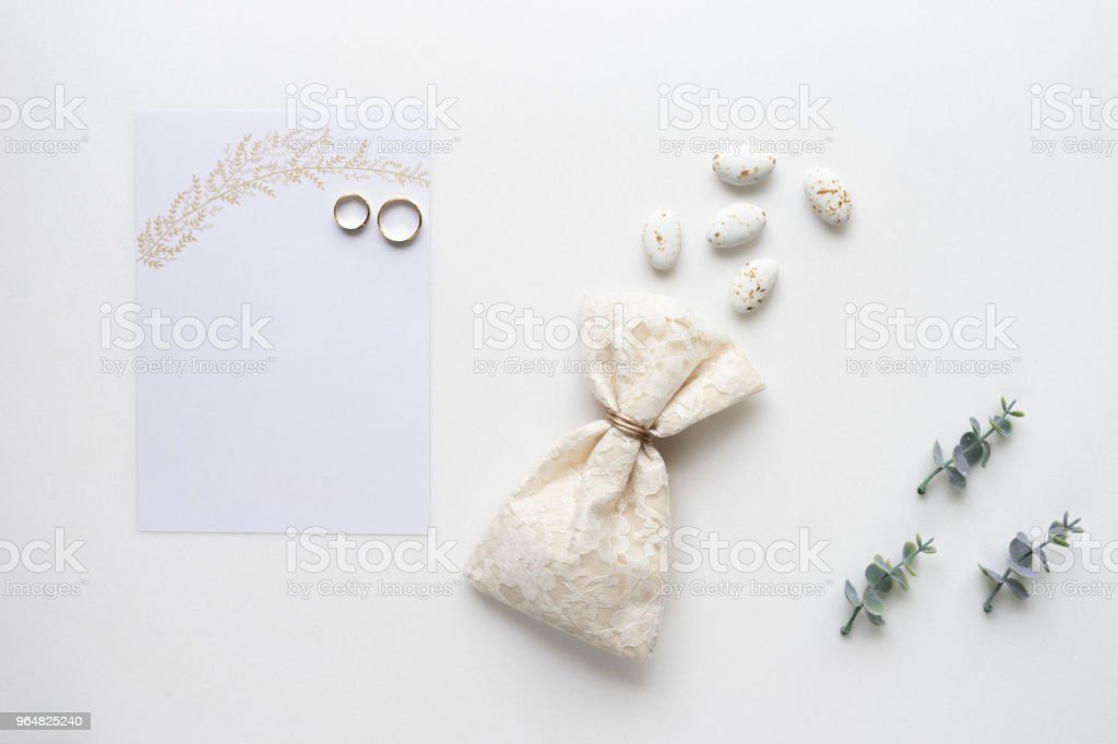 Wedding invitation card, candy, rings and oregano branches. Top view. royalty-free stock photo