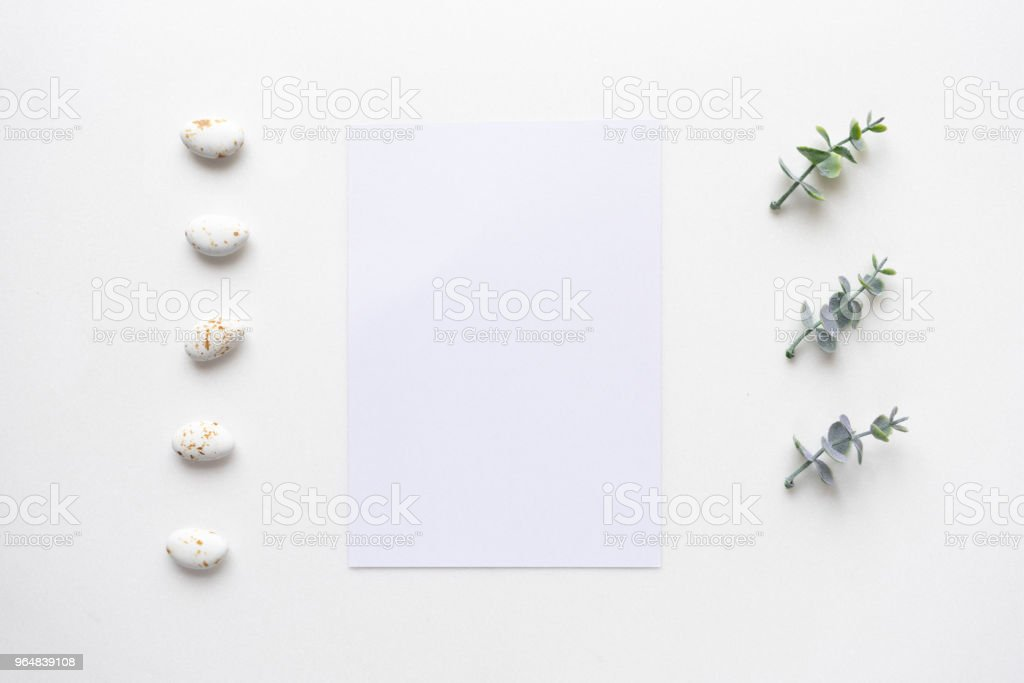 Wedding invitation card on white marble with oregano branches. Top view. royalty-free stock photo