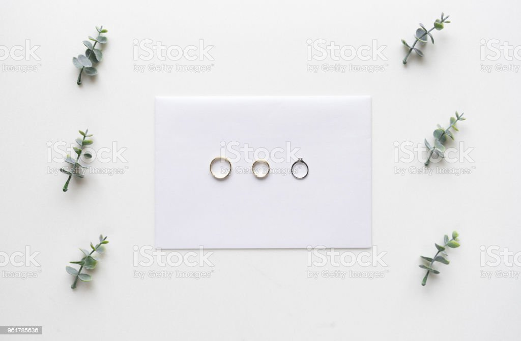 Wedding invitation card on white marble with wedding rings and oregano branches. Top view. royalty-free stock photo