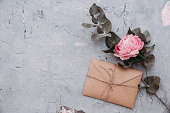 istock Wedding invitation cards, craft envelopes, pink flowers and green leaves on stone background. Overhead view. Flat lay, top view invitation card. 1130999509
