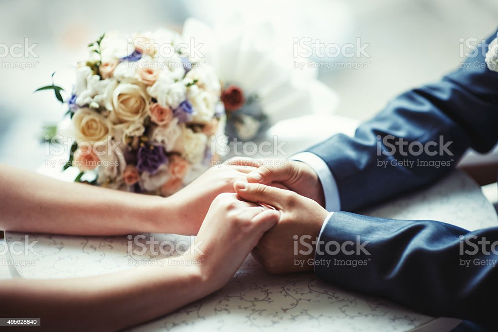 Wedding invitation of a close-up of the couple holding hands stock photo