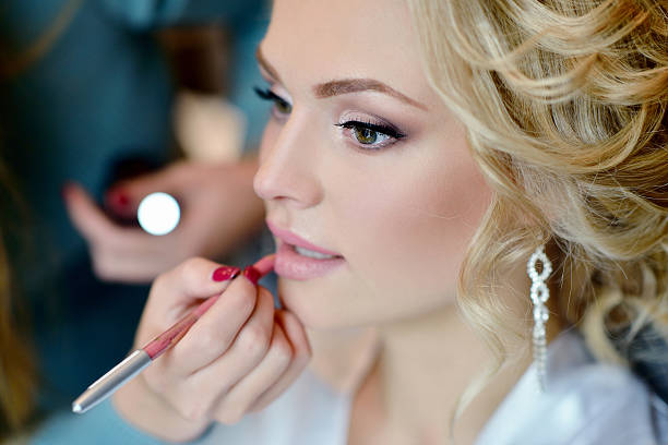 Wedding makeup artist making a make up for bride Wedding makeup artist making a make up for bride. Beautiful sexy model girl indoors. Beauty woman with curly hair. Female portrait. Bridal morning of a cute lady. Close-up hands near face stage make up stock pictures, royalty-free photos & images