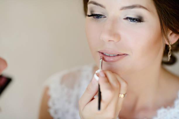 Wedding makeup artist making a make up for bride stock photo