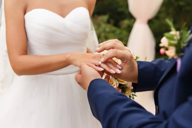 "Wedding, Marriage concept. Groom puts Wedding Ring on Bride""u2019s finger on Wedding Ceremony stock photo"