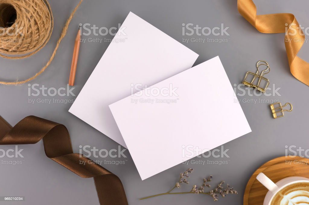 A wedding mock up concept. Wedding Invitation, envelopes, cards Papers on grey background with ribbon and decoration. Top view, flat lay, copy space royalty-free stock photo