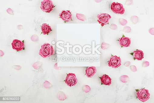 istock Wedding mockup with white paper list, pink rose flowers and petals. Beautiful floral pattern. Flat lay style. 825250222