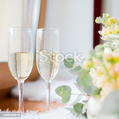 Wedding morning, two glasses of champagne and bride's bouquet of peony and roses, lots of greenery.