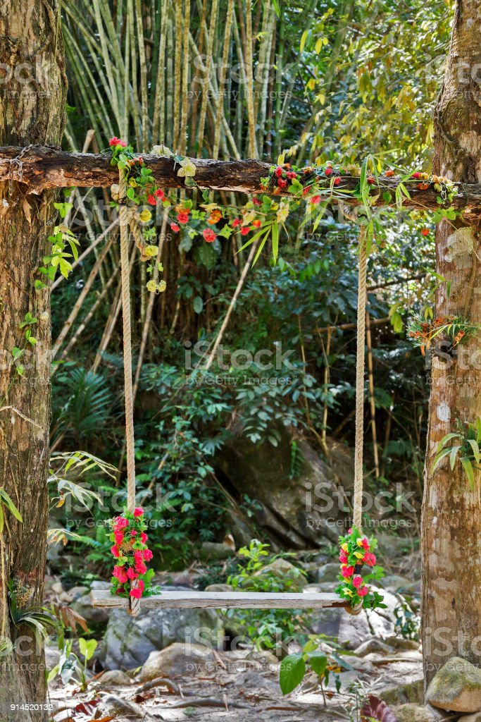 Wedding pergola seesaw lonely swing decorated with flowers at garden stock photo