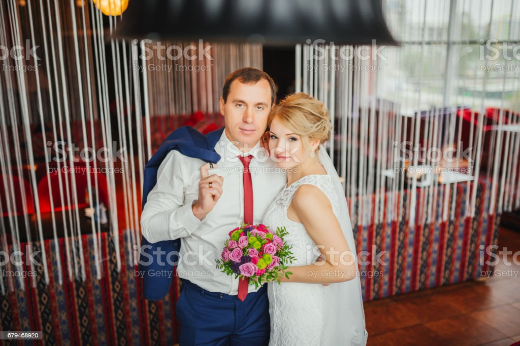 Wedding photo session in interior. Bridal couple, Happy Newlywed woman and man embracing. Romantic wedding in luxury apatment. Wedding day. royalty-free stock photo