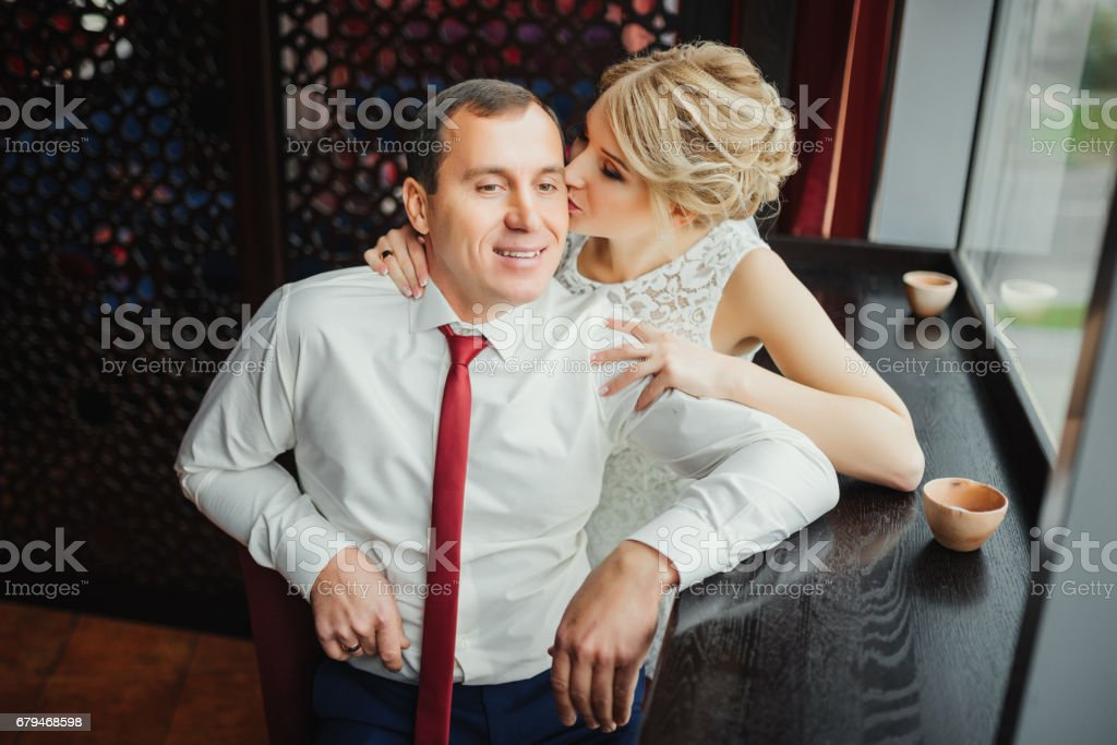 Wedding photo session in interior near the window. Bridal couple, Happy Newlywed woman and man embracing. Romantic wedding. Wedding kiss. royalty-free stock photo