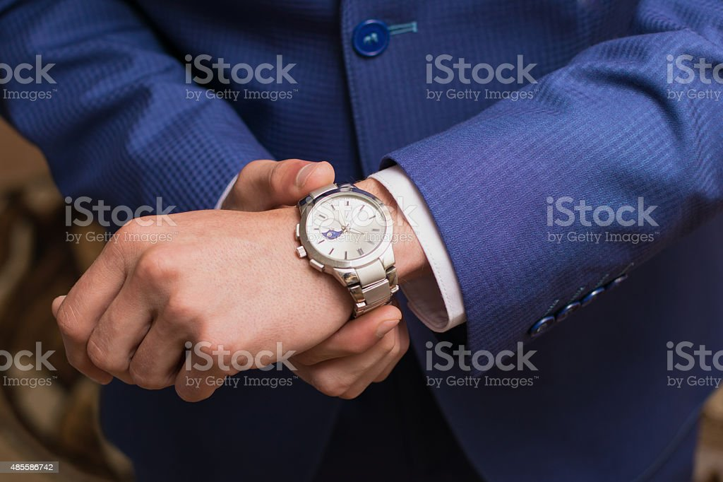 wedding photo. The groom puts on hours stock photo