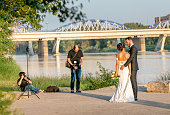 ZARAGOZA, SPAIN - 14 JULY 2018: wedding photographer and videographer taking photo and video of bride and groom in city near Ebro river and Pilar Cathedral