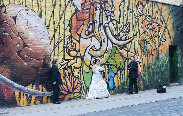 hochzeit-fotograf & kunden vor graffiti-wand. - heiratssprüche stock-fotos und bilder