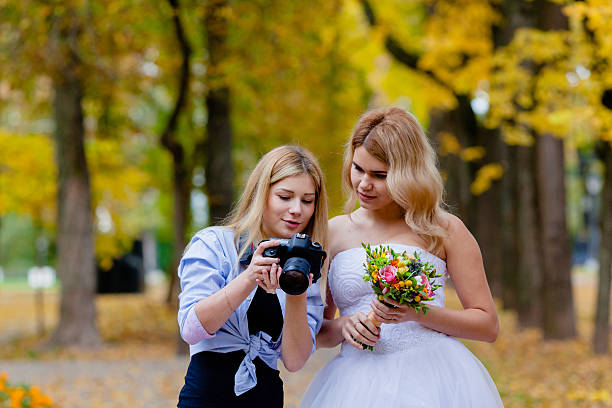 Wedding photographer discussing with the bride recently taken photos stock photo