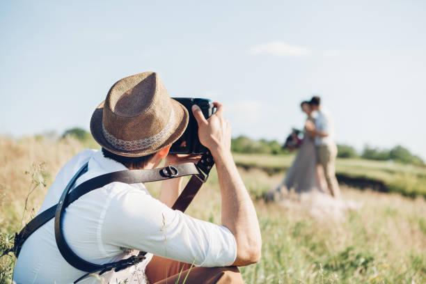 hochzeitsfotograf fotografiert von braut und bräutigam in der natur, fine art foto - hochzeitsbilder stock-fotos und bilder