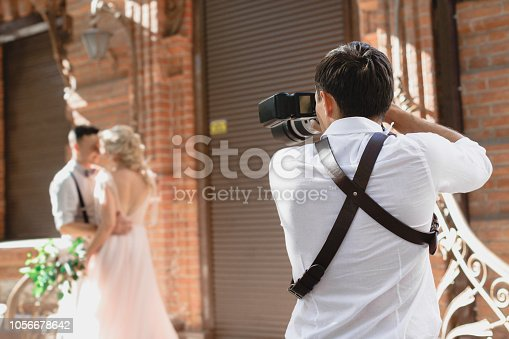 istock wedding photographer takes pictures of bride and groom 1056678642