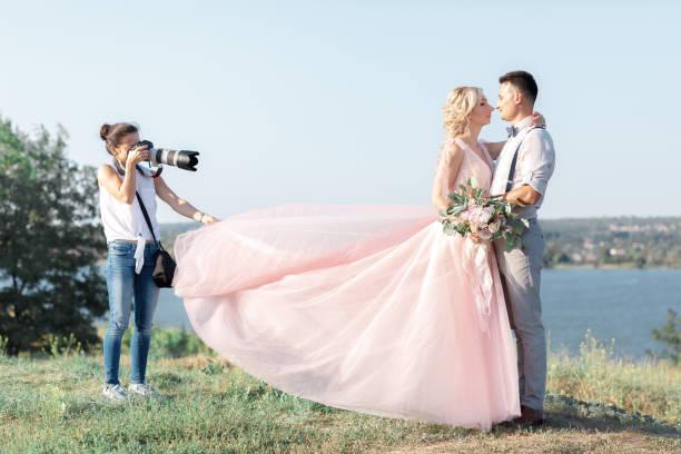 hochzeitsfotograf nimmt bilder der braut und des bräutigams - hochzeitsbilder stock-fotos und bilder