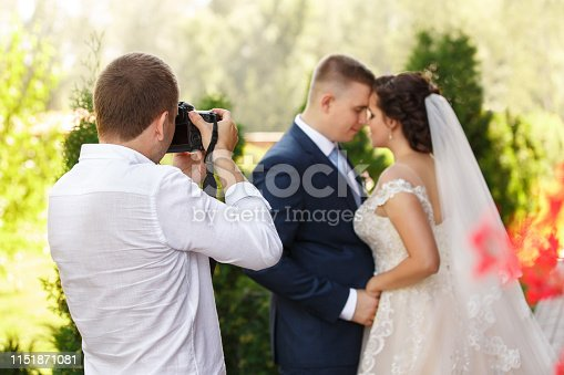 Wedding photographer with camera takes pictures of the beautiful bride and groom outdoors