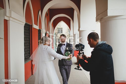 Professional wedding photographer taking pictures of the bride and groom in a gallery
