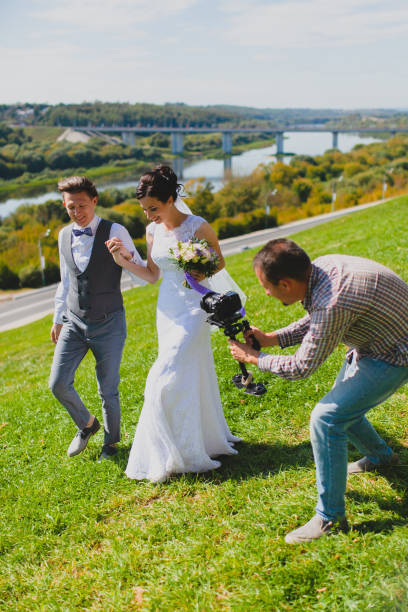 Wedding photographer taking pictures of the bride and groom on a hillside stock photo