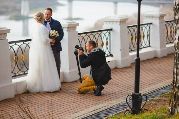 Wedding photographer taking pictures of the bride and groom on park alley stock photo