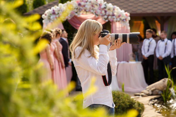 Wedding photographer with a professional camera working at a wedding ceremony stock photo
