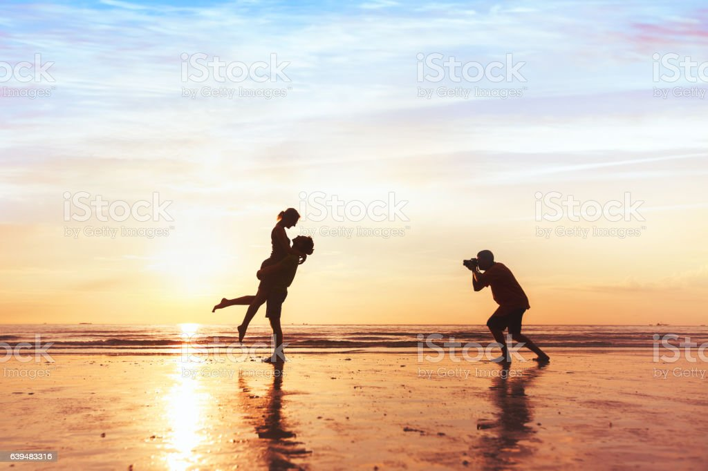 wedding photographer working with couple on the beach stock photo